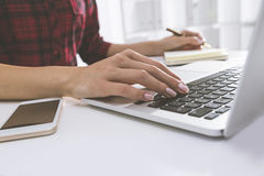 Woman in red checkered shirt is typing with one hand. Close up of woman in red checkered shirt typing with one hand. White bookcase with folders is seen at the Royalty Free Stock Image