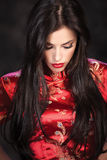 Woman in red Cheongsam on dark background Stock Images