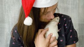 Woman in red Christmas cap with white rat. Beautiful young woman in red Christmas cap holding white rat in arms and show it to camera stock footage