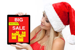 Woman red Christmas hat holding tablet computer  with big sale Royalty Free Stock Photos