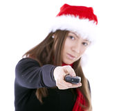 Woman in red Christmas hat keeping tv pilot Royalty Free Stock Photo
