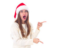 Woman in red christmas hat pointing on something. Young pretty woman in white sweater with red christmas hat pointing on something on white background in studio Stock Images