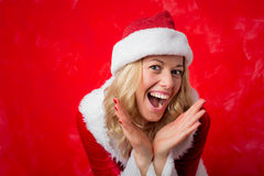 Woman in red Christmas hat showing her surprise Stock Photography