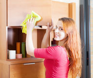 Woman in red cleaning wooden furiture Royalty Free Stock Images