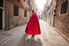 A woman in a red cloak hurries down the street of Venice. A woman in a red cloak is hurrying down the street of Venice. On the way to the casino. Sunny in Venice Stock Images