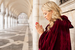 Woman in red cloak praying royalty free stock images