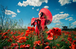 Woman in red clothes in the poppy field Stock Photo