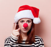 Woman with red clown nose. Portrait of a young redhead woman in Santa Claus hat with red clown nose on pink background Stock Photography