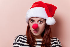 Woman with red clown nose. Portrait of a young redhead woman in Santa Claus hat with red clown nose on pink background Stock Image