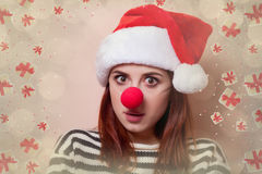 Woman with red clown nose. Portrait of a young redhead woman in Santa Claus hat with red clown nose on pink background Royalty Free Stock Images
