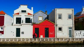 Woman with a red coat in front of a red house in Aveiro, Portugal royalty free stock photography