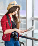 Woman in a red coat and hat standing in the terminal or at the station with a suitcase and looking at the map. Stock Image