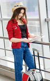 Woman in a red coat and hat standing in the terminal or at the station with a suitcase and looking at the map. Royalty Free Stock Image