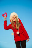 Woman in red coat holding heart shape Royalty Free Stock Images