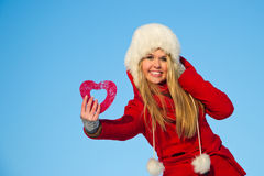 Woman in red coat holding heart shape Royalty Free Stock Photo