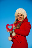 Woman in red coat holding heart shape Stock Photography