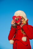 Woman in red coat looking through heart shape Stock Photos