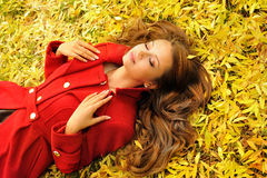 Woman in red coat lying in autumn leaves. Stock Photo