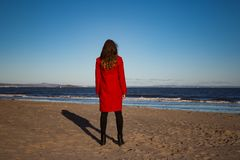 Woman in red coat on sandy beach. Back of brown haired woman standing in red coat on sandy beach with waves in blue water on sunny day on Portobello Beach Stock Image