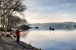 Woman in a red coat on the shore of Windermere Stock Photography