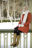 Woman in red coat sit at boundary Royalty Free Stock Images