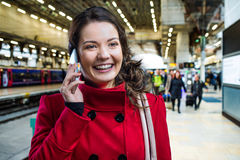 Woman in red coat on train station talking on phone Royalty Free Stock Photo