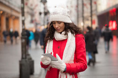 Woman in red coat and wool cap and gloves with smartphone in han Stock Photo