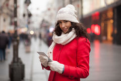 Woman in red coat and wool cap and gloves with smartphone in han. Beautiful Woman in Red Coat and and wool cap and gloves read messages on smartphone and smiling Royalty Free Stock Image