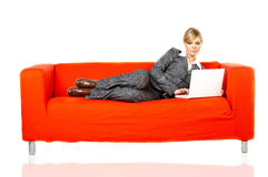 Woman on red couch Stock Images
