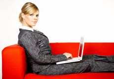 Woman on red couch Royalty Free Stock Photography