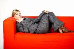 Woman on red couch Stock Image