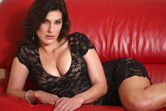 Woman on red couch. A sexy woman wearing black on a red couch Royalty Free Stock Images