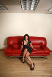 Woman on red couch. A sexy woman wearing black on a red couch Royalty Free Stock Photography