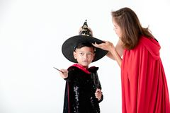 Woman in red cover with hood taking care for boy in costume dress of witch and holding magic wand stick in hand on white royalty free stock photos