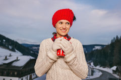 Woman with red cup on balcony overlooking mountains in evening Royalty Free Stock Photography