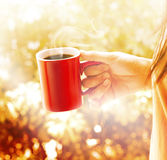Woman with red cup of coffee vibrant brown background Stock Photography