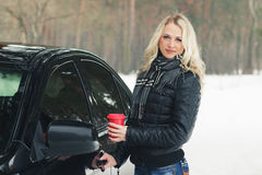 Woman with a red cup of hot drink keeps the car door handle Royalty Free Stock Photo