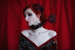 A woman with red curly hair in a black dress and retro makeup on a red background. Red-haired girl with pale skin, blue eyes, a bright unusual appearance, red Royalty Free Stock Images