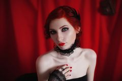 A woman with red curly hair in a black dress and retro makeup on a red background. Red-haired girl with pale skin, blue eyes, a bright unusual appearance, red Royalty Free Stock Image