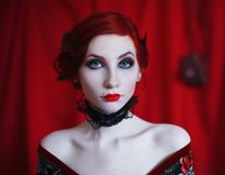 A woman with red curly hair in a black dress and retro makeup on a red background. Stock Images