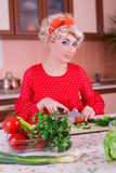 Woman in red cutting vegetables Royalty Free Stock Photography