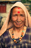 Woman with red dots in Nepal. Dolpo, Nepal - circa June 2012: Native woman dressed in purple shirt with necklace made of beads and with headcloth and large red Royalty Free Stock Photo
