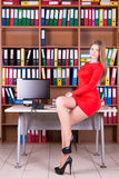 Woman in red drees sitting on the desk Royalty Free Stock Photography