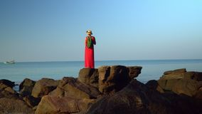 The woman in red in a dress with a backpack costs having straightened hands on big black stones at the coast of the stock video footage
