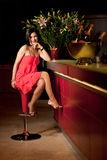 Woman red dress at bar counter smiling Stock Photo
