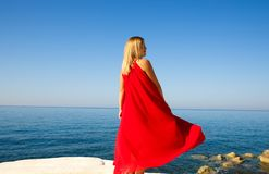 Woman in red. Woman in the red dress at the beach in Cyprus Royalty Free Stock Image