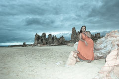 Woman in red dress at beach with dark storm clouds Stock Photo