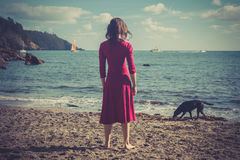 Woman in red dress on beach with dog Stock Photo