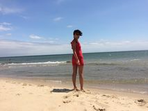 Woman in a red dress on a beach  Stock Photography