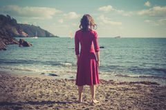 Woman in red dress on a beach Stock Photo